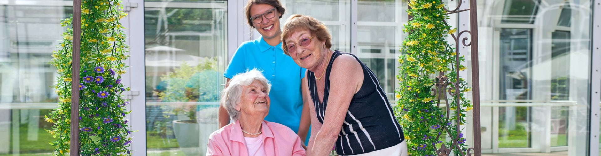 two elderly women and a caregiver